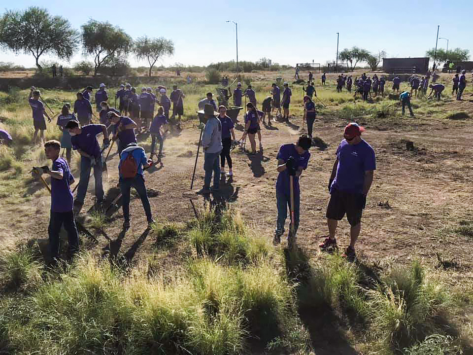 Residents and volunteers rake and clear weeds during the Surprise Day of Service event.