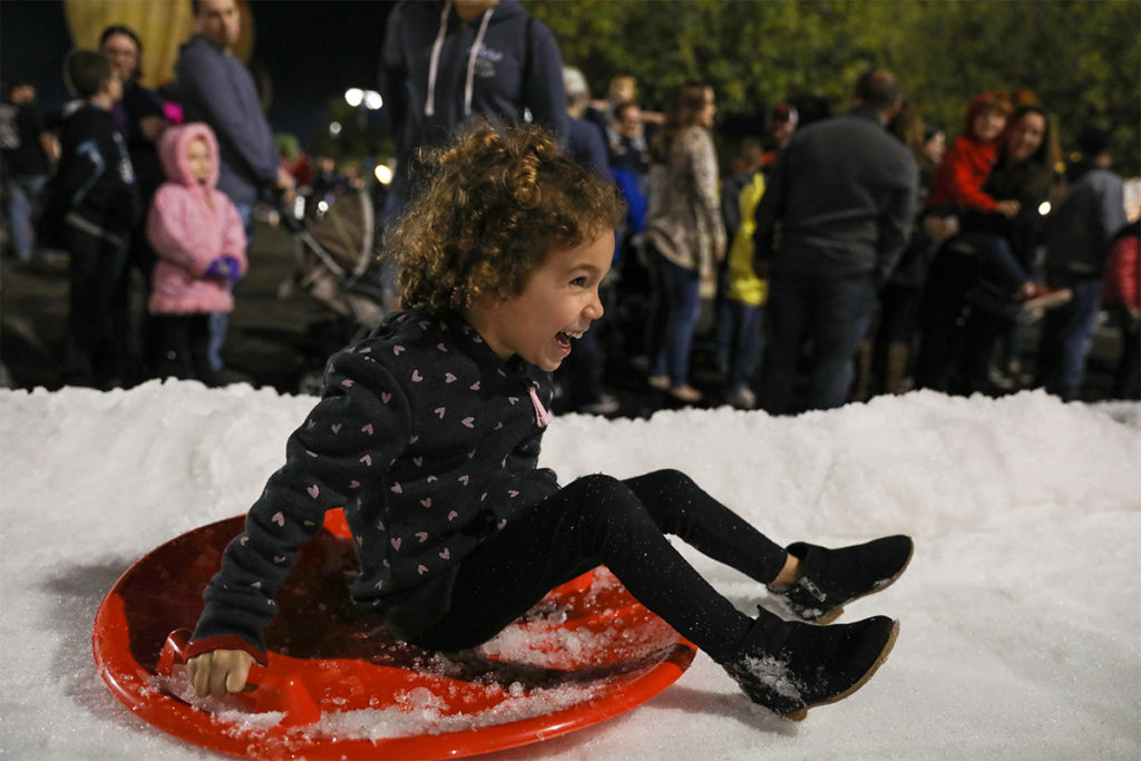 A young girl laughs as she rides a sled down a snow slide at Surprise Party.