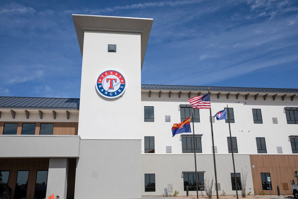 The United States, Arizona and Texas Ranges flags waive in front of the Texas Rangers housing building.