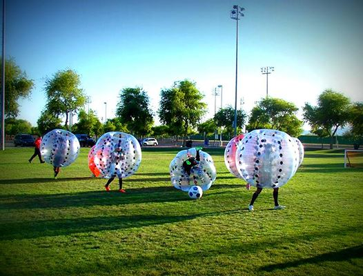 Children inside inflated bubbles playing soccer.