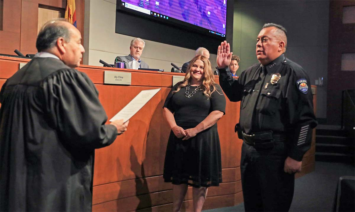 Chief Benny Pina holds up his right hand and takes the oath of office from Judge Dominguez.